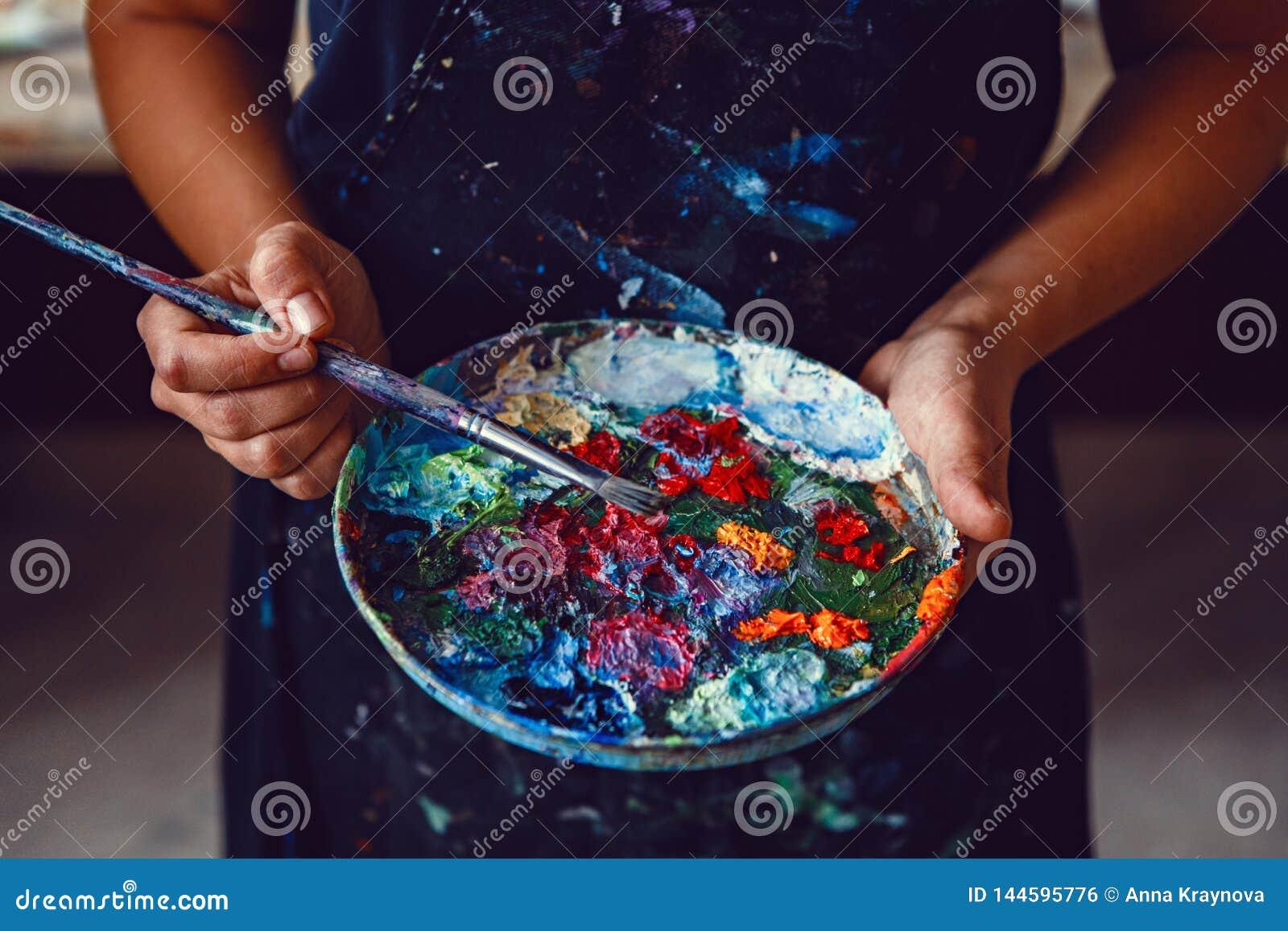 Руки женского художника держа грязную грязную палитру с различными красками и paintbrush