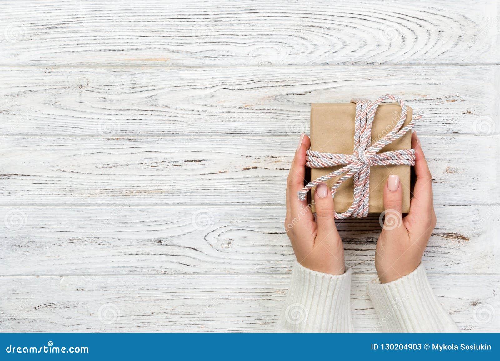 Руки женщины дают в оболочке Валентайн или другой настоящий момент праздника handmade в бумаге с розовой лентой Присутствующая ко
