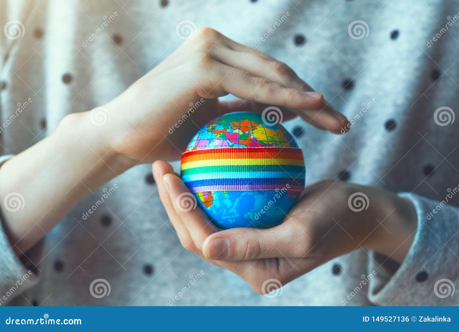 Руки женщины держа глобус с лентой радуги LGBT
