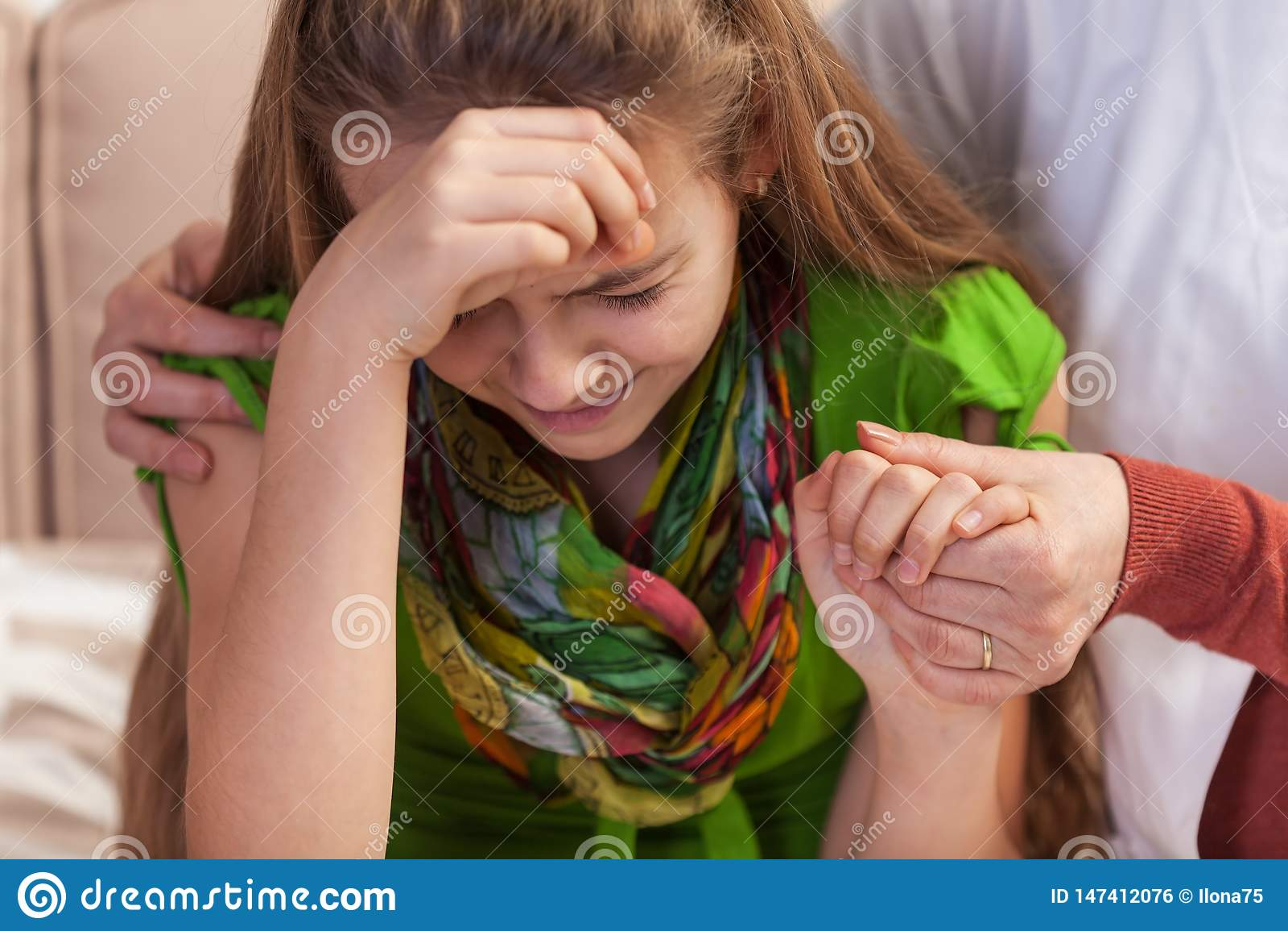 Руки женщины держа и утешая плача маленькую девочку Подростковые проблемы концепция, конец вверх