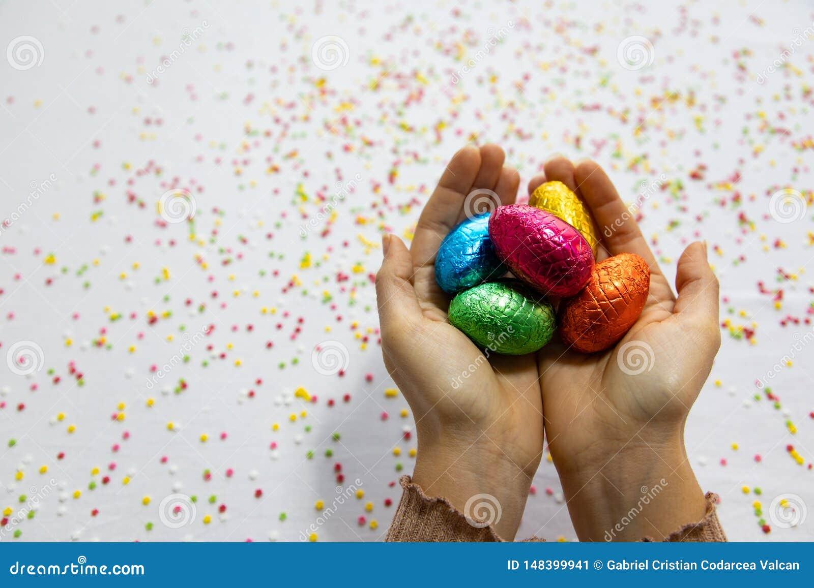 Руки женщины держа красочные пасхальные яйца шоколада с белой предпосылкой и красочный запачканный confetti