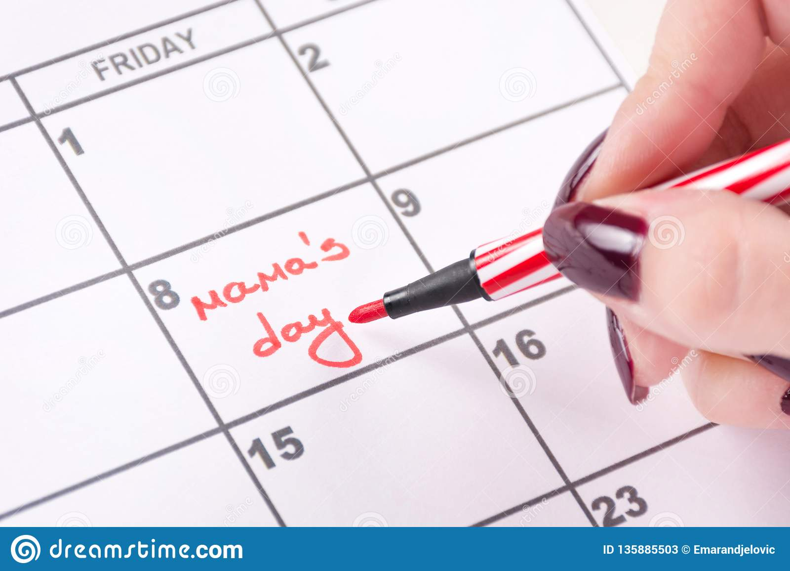 Руки женщины с красной чувствуемой ручкой пишут мамам слов день в календаре