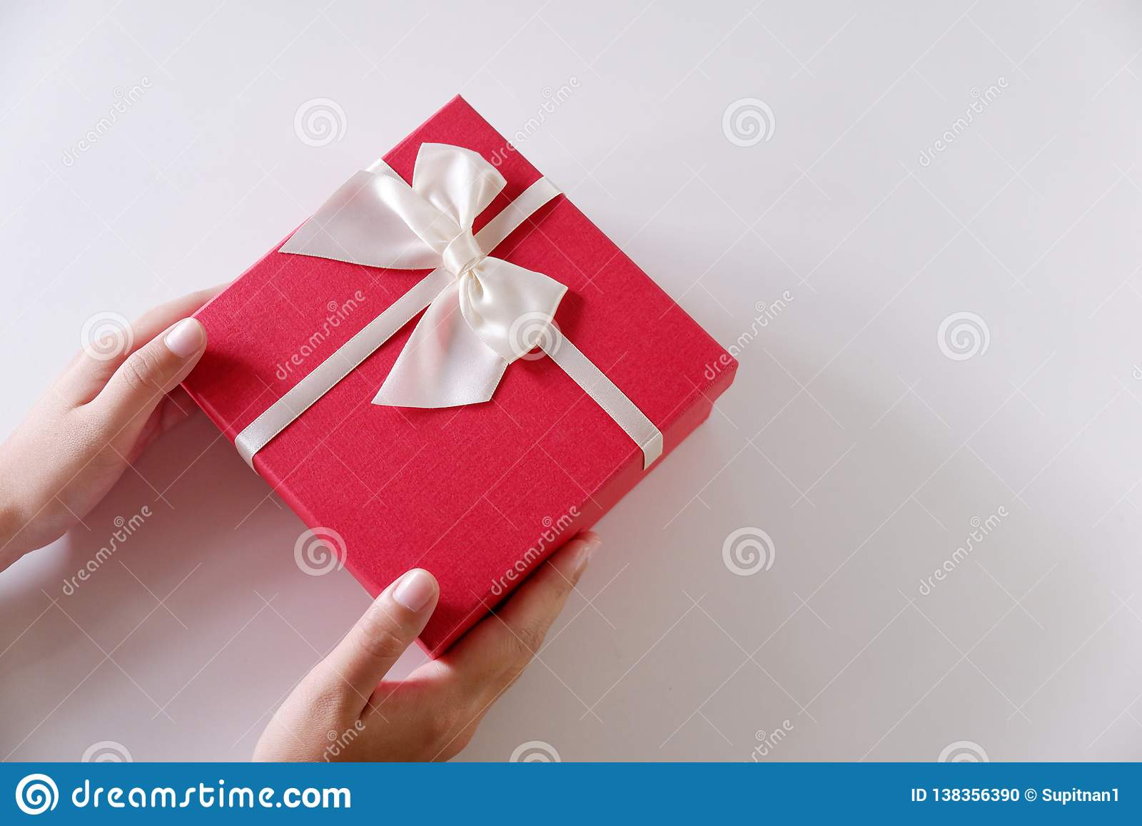 Руки женщин конца-вверх отправляя красную подарочную коробку с белой лентой на белой предпосылке