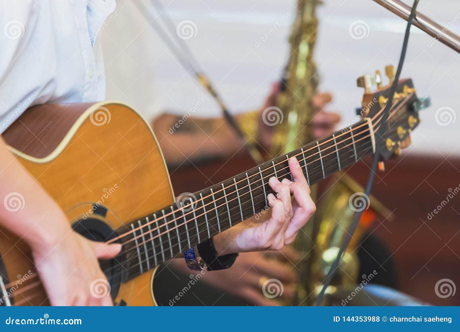 Руки играя акустическую гитару, конец вверх