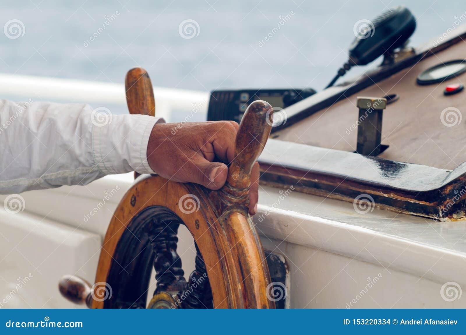 Руки капитана держа колесо на палубе корабля