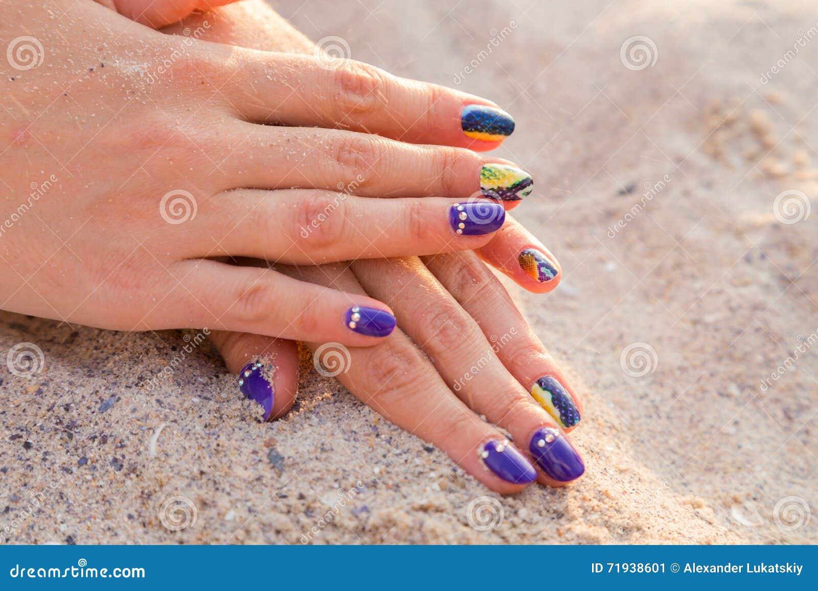 Руки красивых женщин с профессиональным маникюром на песке