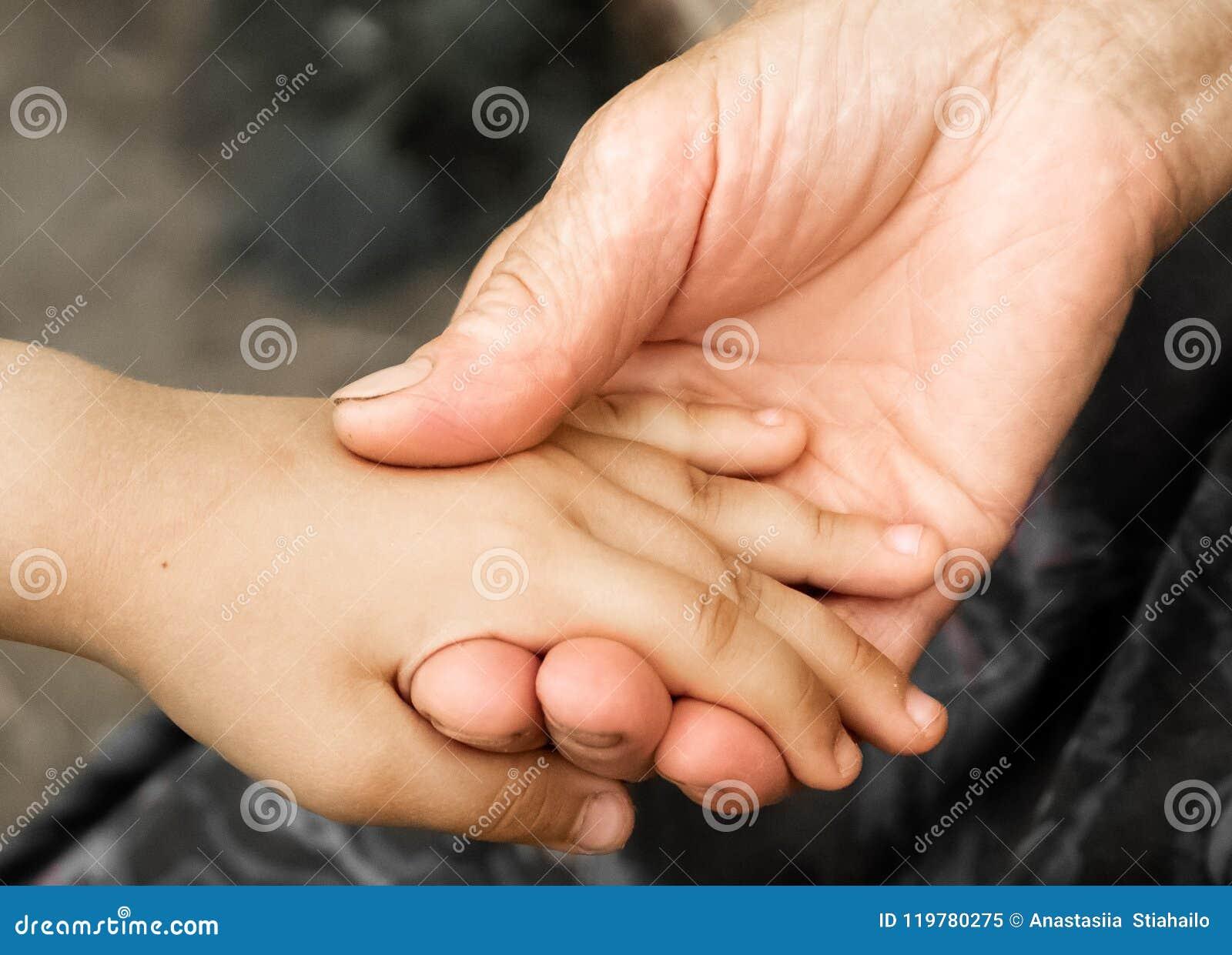 Руки маленькой девочки и старой бабушки Руки маленьких ребеят держа пожилого человека, концепции дня доброты мира