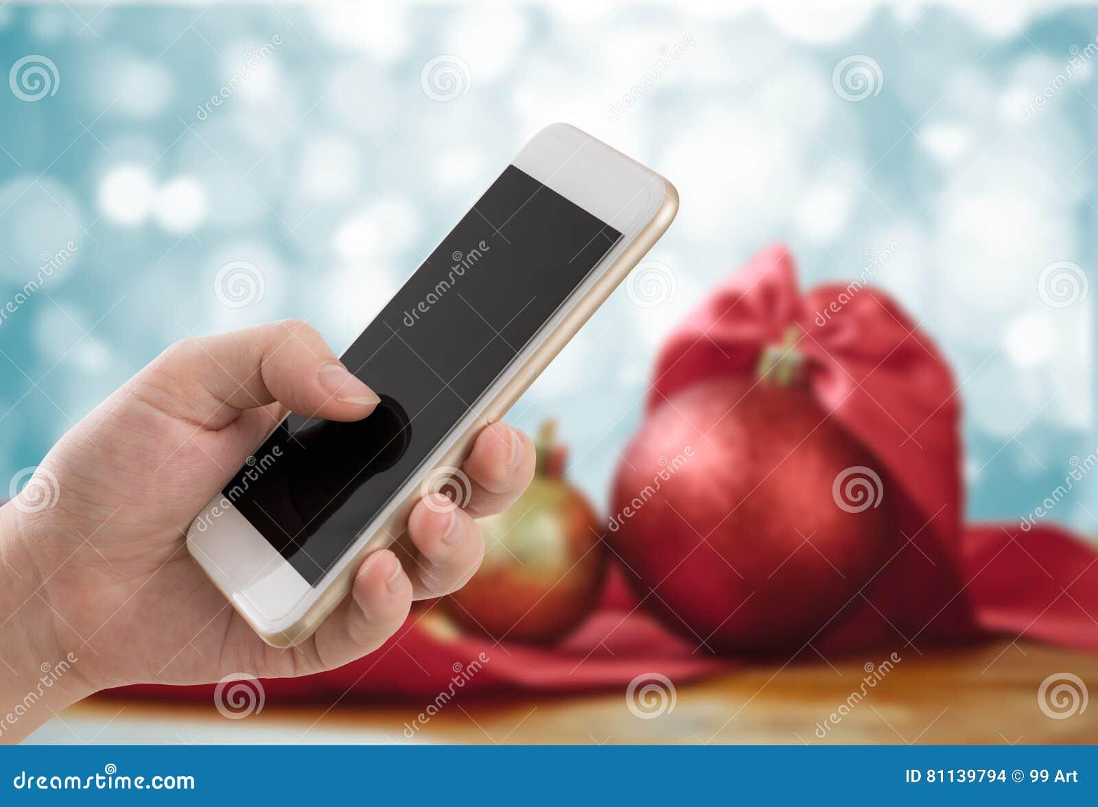 Руки молодой женщины используя мобильный телефон с backgro рождества