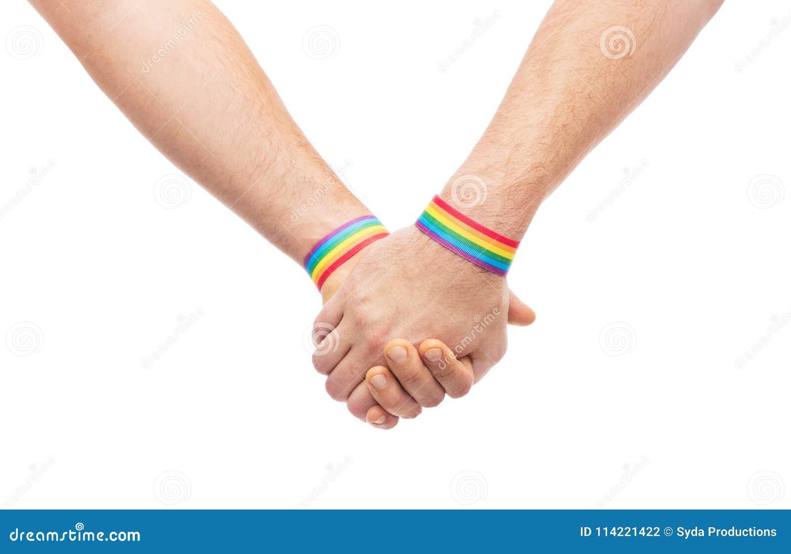 Руки пар с wristbands радуги гей-парада