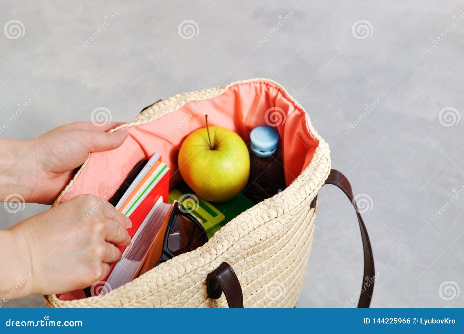 Руки принимают стильную модную плетеную сумку с учебниками и тетрадями, коробкой для завтрака и зеленым Яблоком, водой для закуск