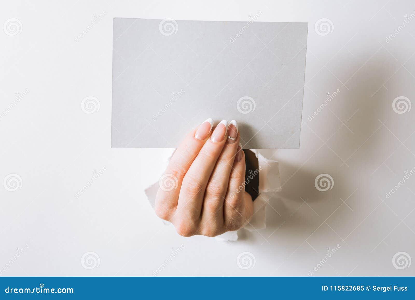 Руки при визитная карточка пробивая отверстие в белой предпосылке