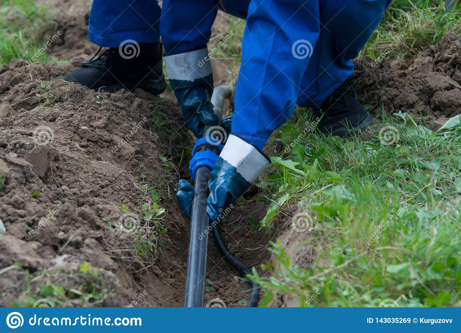 Руки работника, в голубых перчатках, клали пластиковый трубопровод в открытой канаве в земле
