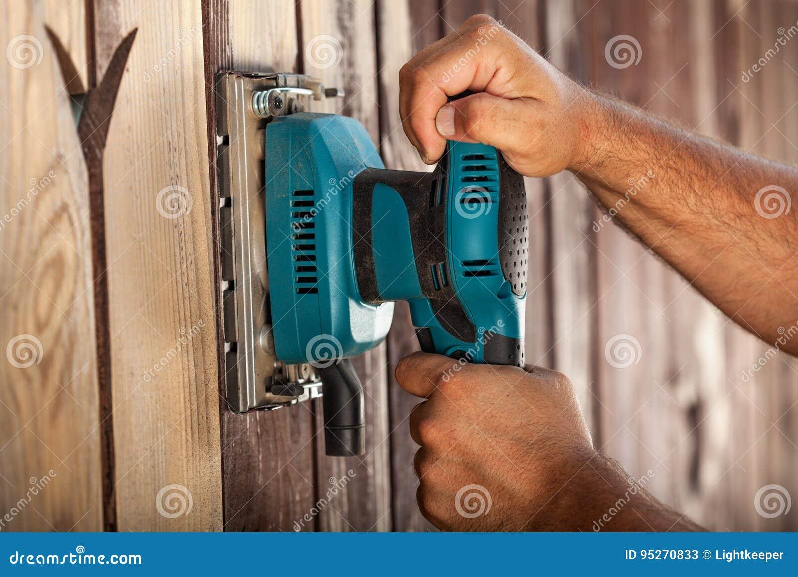 Руки работника используя электрический вибрируя шлифовальный прибор - крупный план