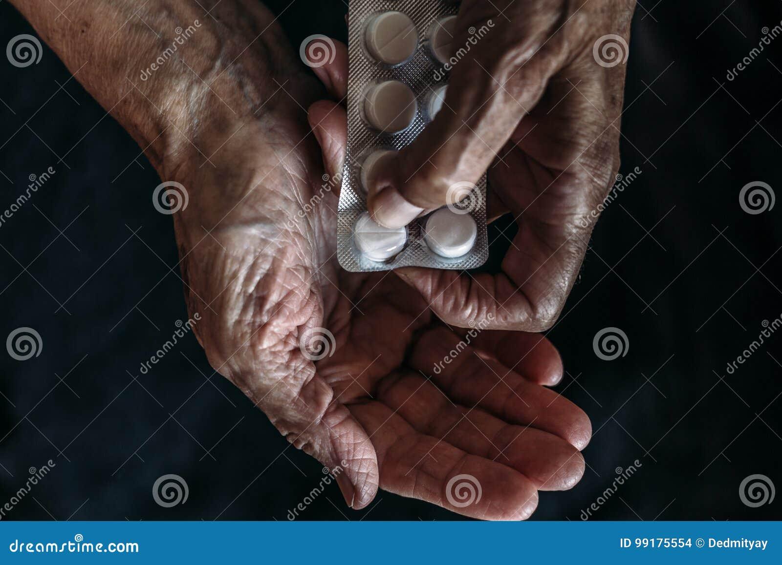 Руки старухи с таблетками или пилюльками Лекарство здравоохранения и принимать старые люди