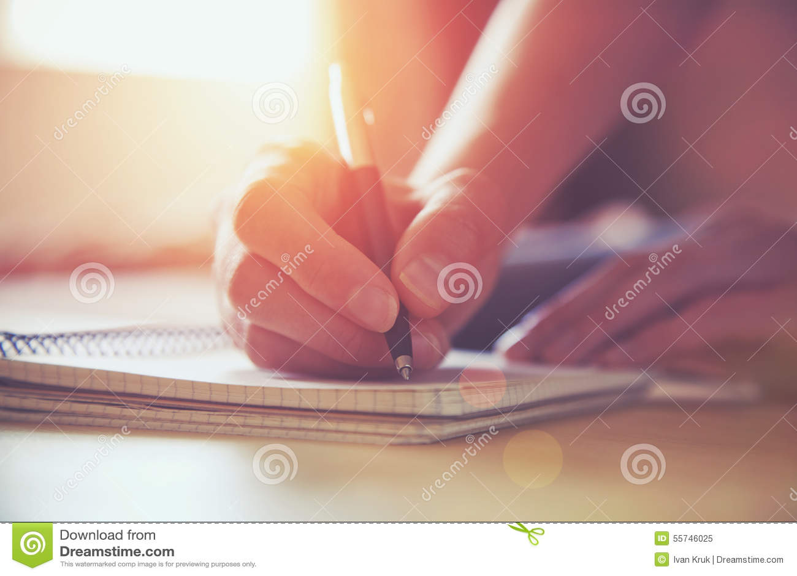 Руки с сочинительством ручки на тетради