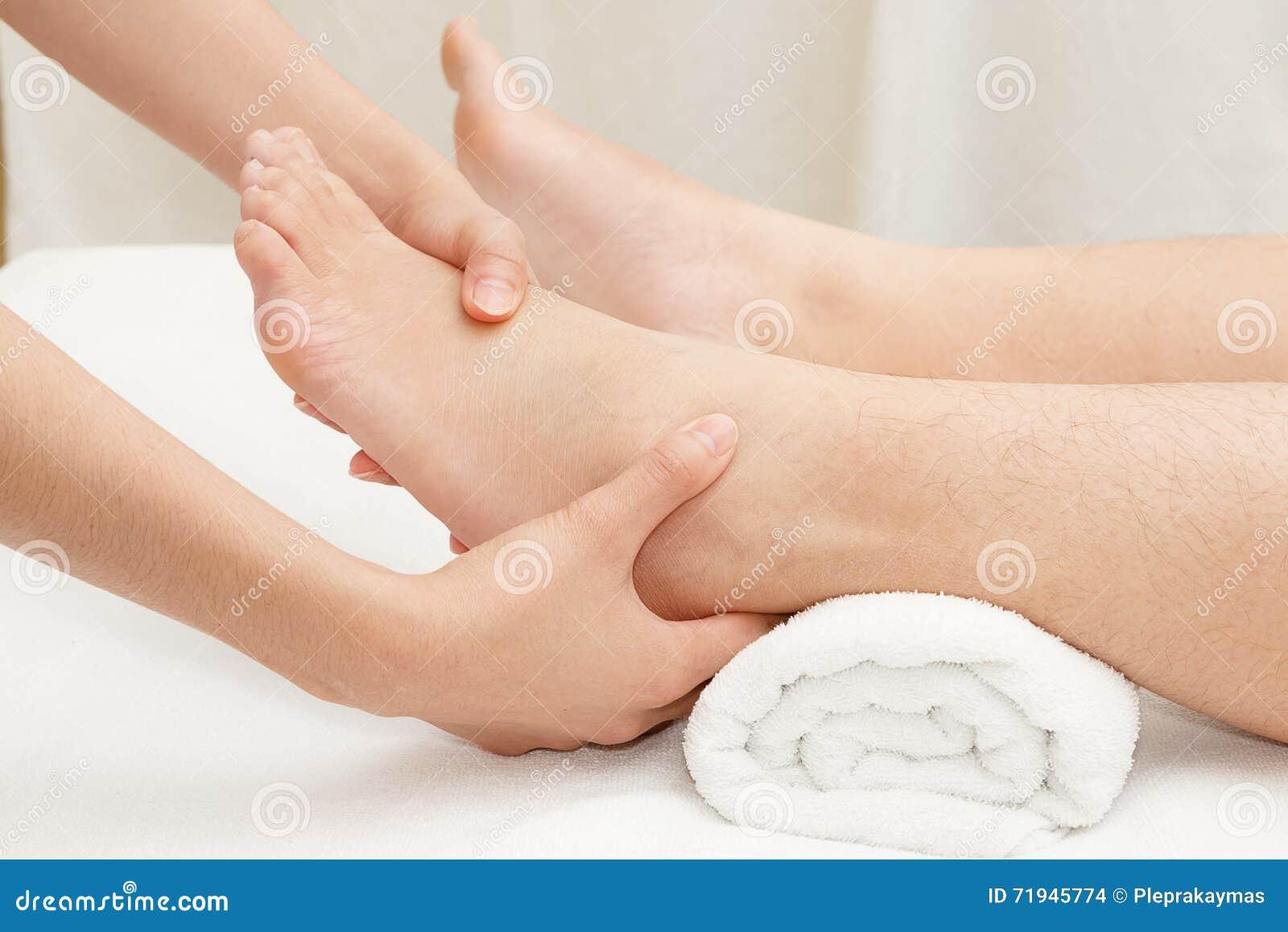 Руки терапевта массажируя женскую ногу