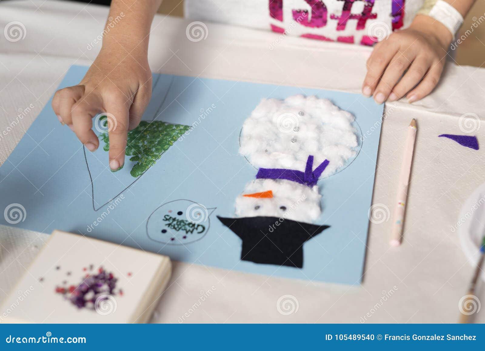 Руки 10-ти летней девушки делая ремесло рождества