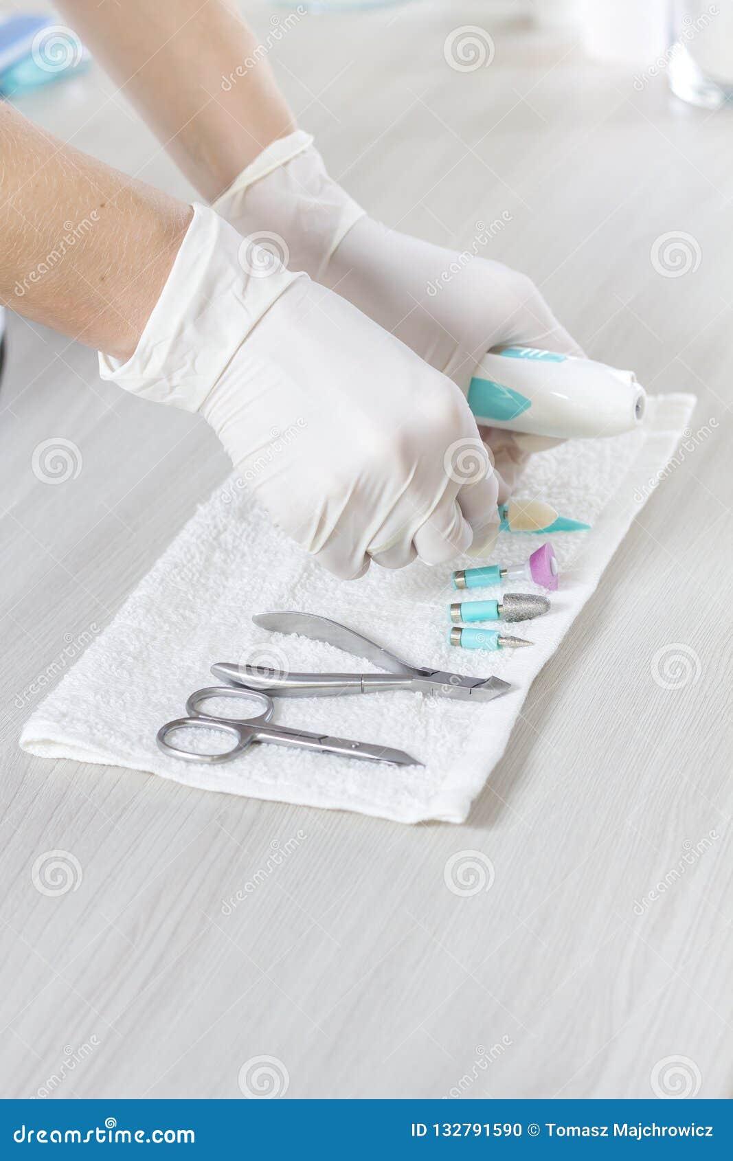Руки beautician в устранимых перчатках положили инструменты косметик на белое полотенце Подготовка для косметической обработки
