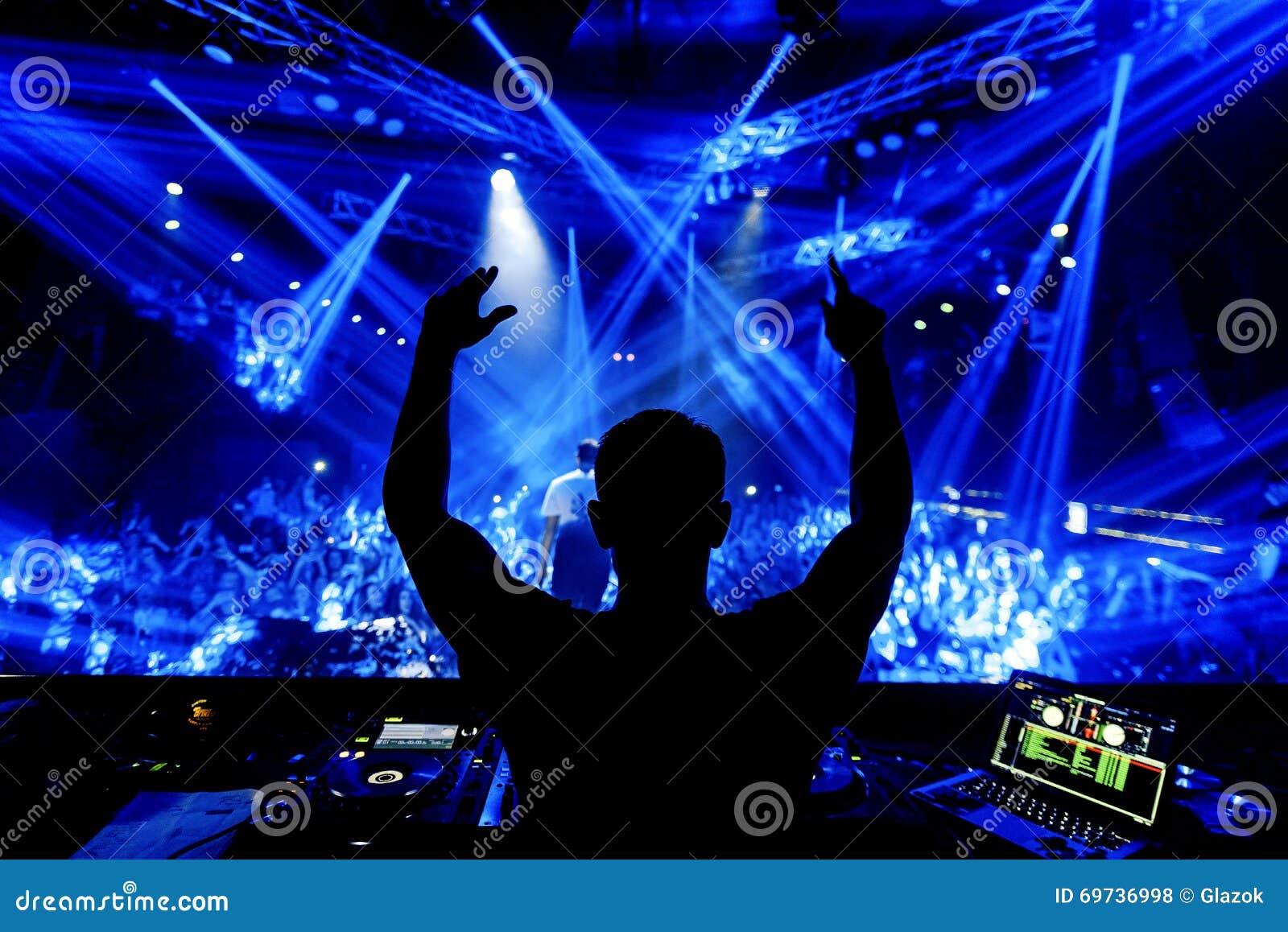 Руки DJ вверх на партии ночного клуба под голубым светом с толпой людей