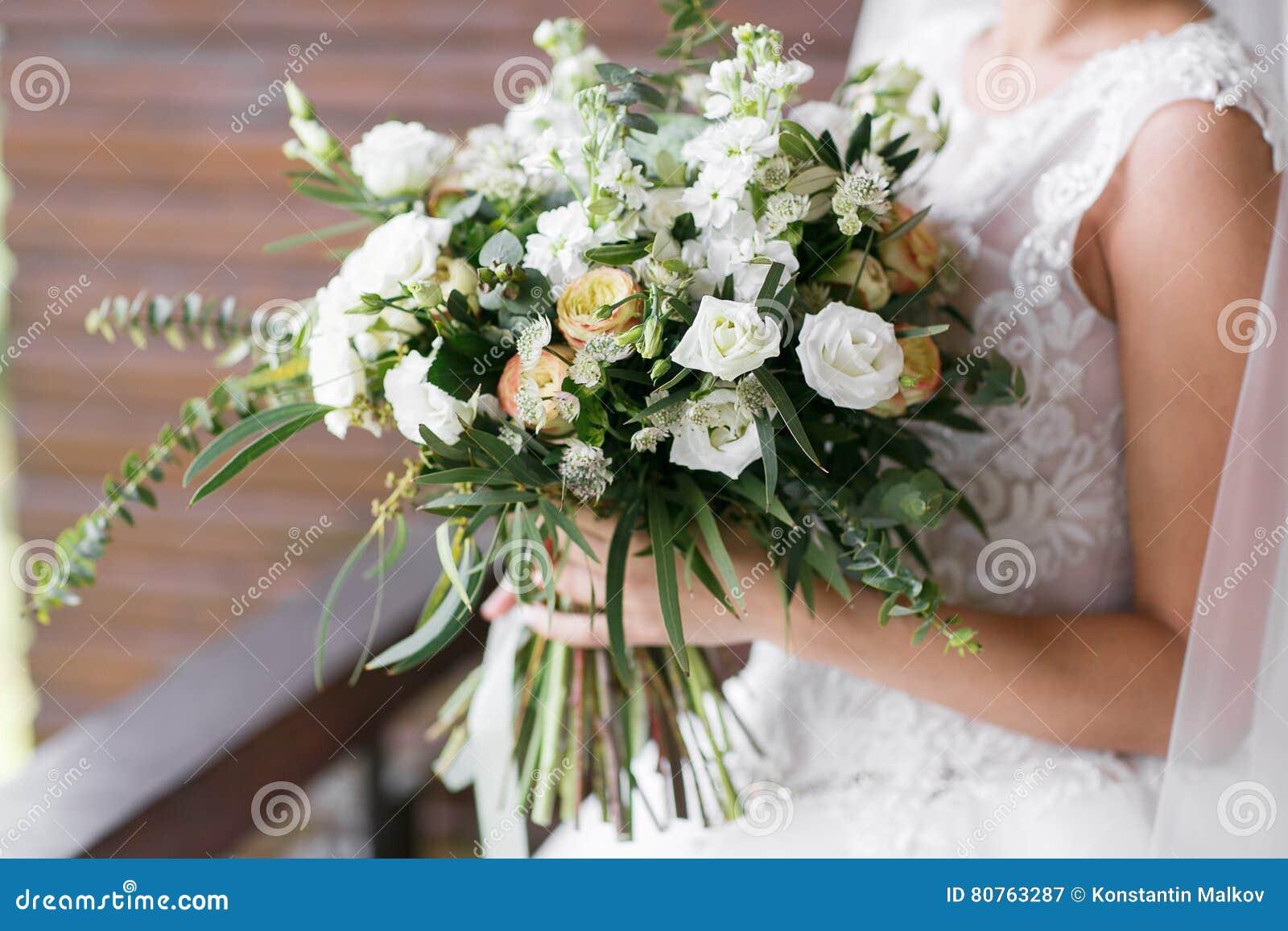 руки groom невесты букета bridal ` S невесты Красивый белых цветков и растительности, украшенный с silk лентой, лежит на годе сбо