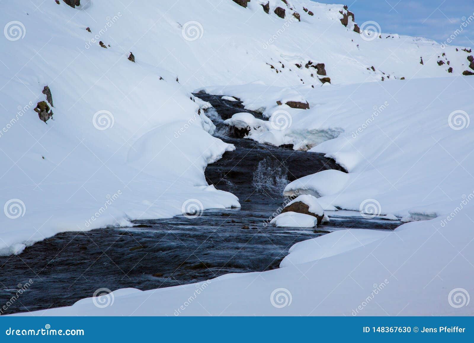 Ручей в снеге в гористых местностях Исландии