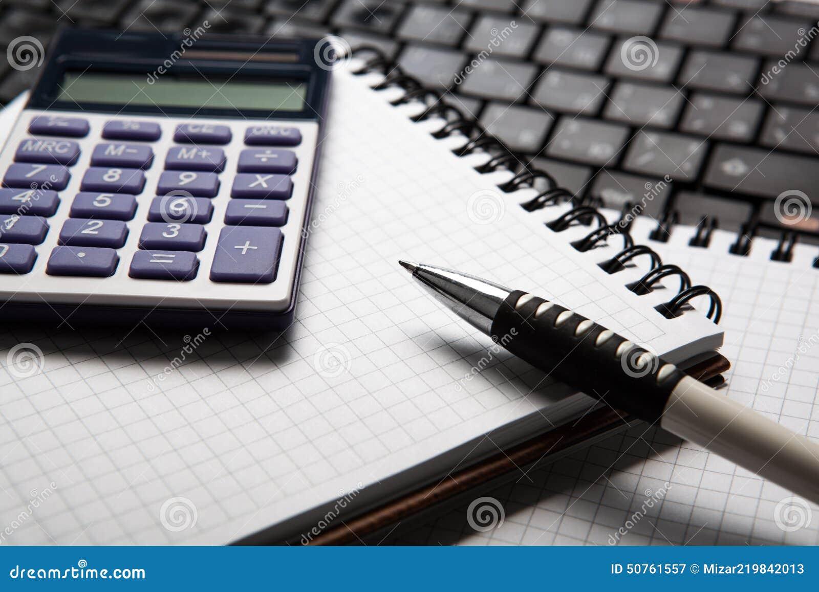 Ручка с калькулятором на тетради и клавиатуре