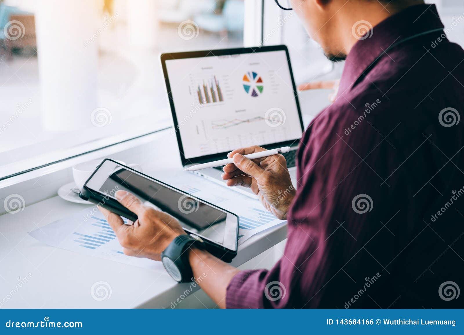 Ручка удерживания человека инвесторов указывая планшет на анализировать диаграммы на ноутбуке компьютера в офисе
