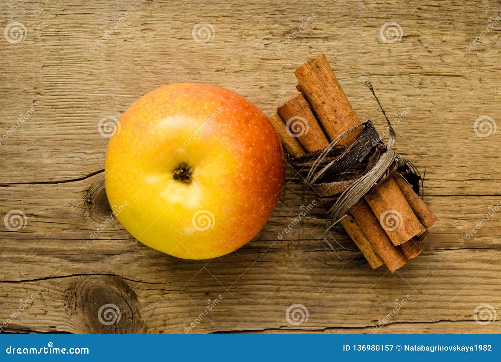 Ручки и яблоко циннамона на ингредиенте деревянного стола