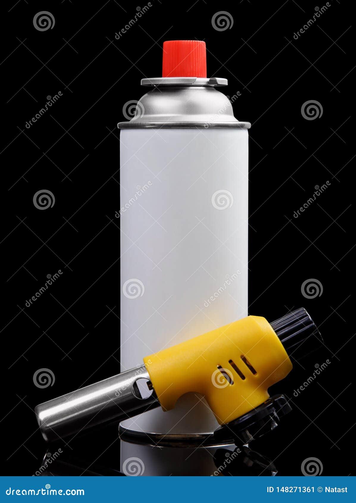 Ручные горелка факела газа и баллончик газа на черноте