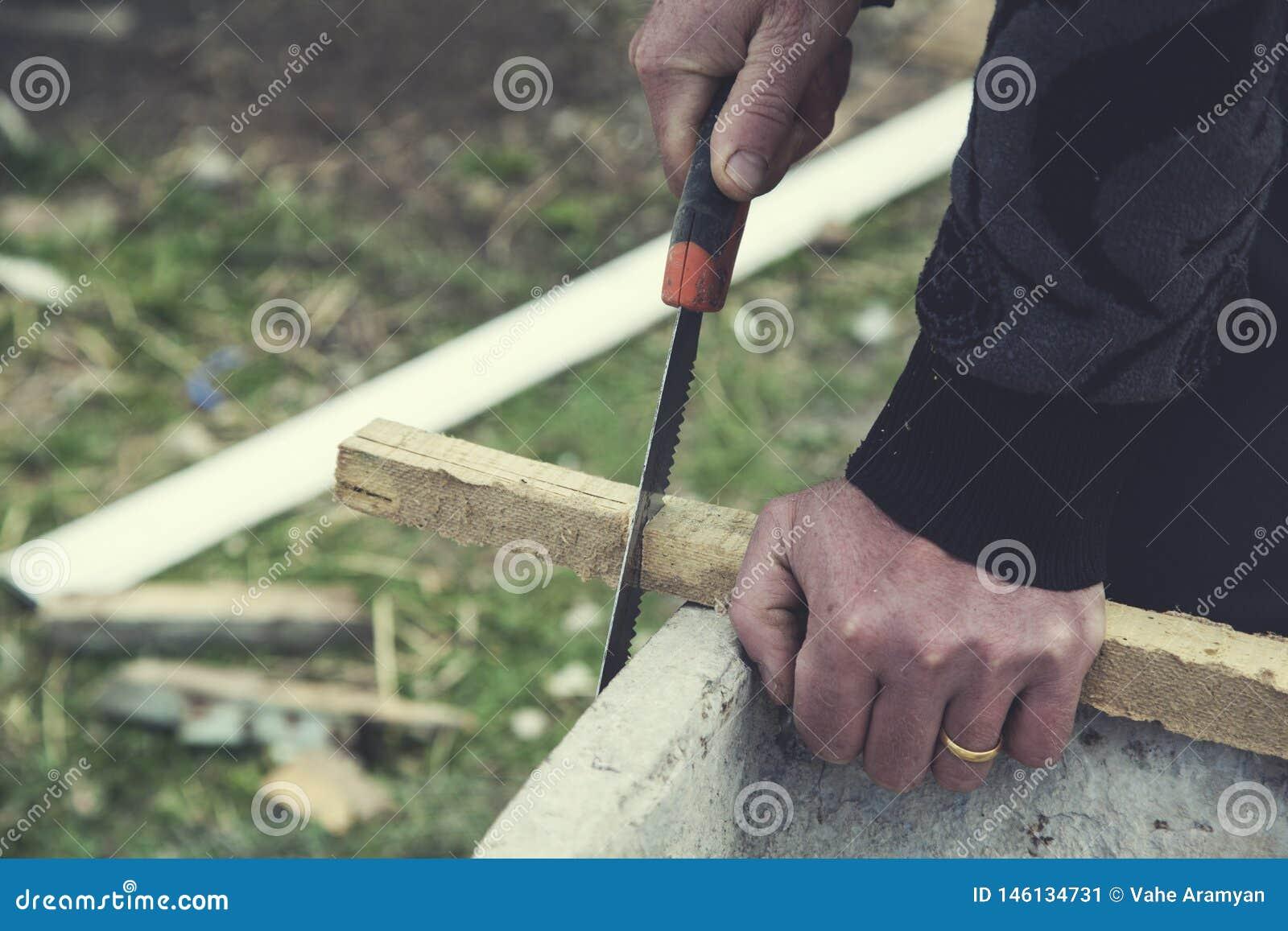 Ручные пилы человека с древесиной