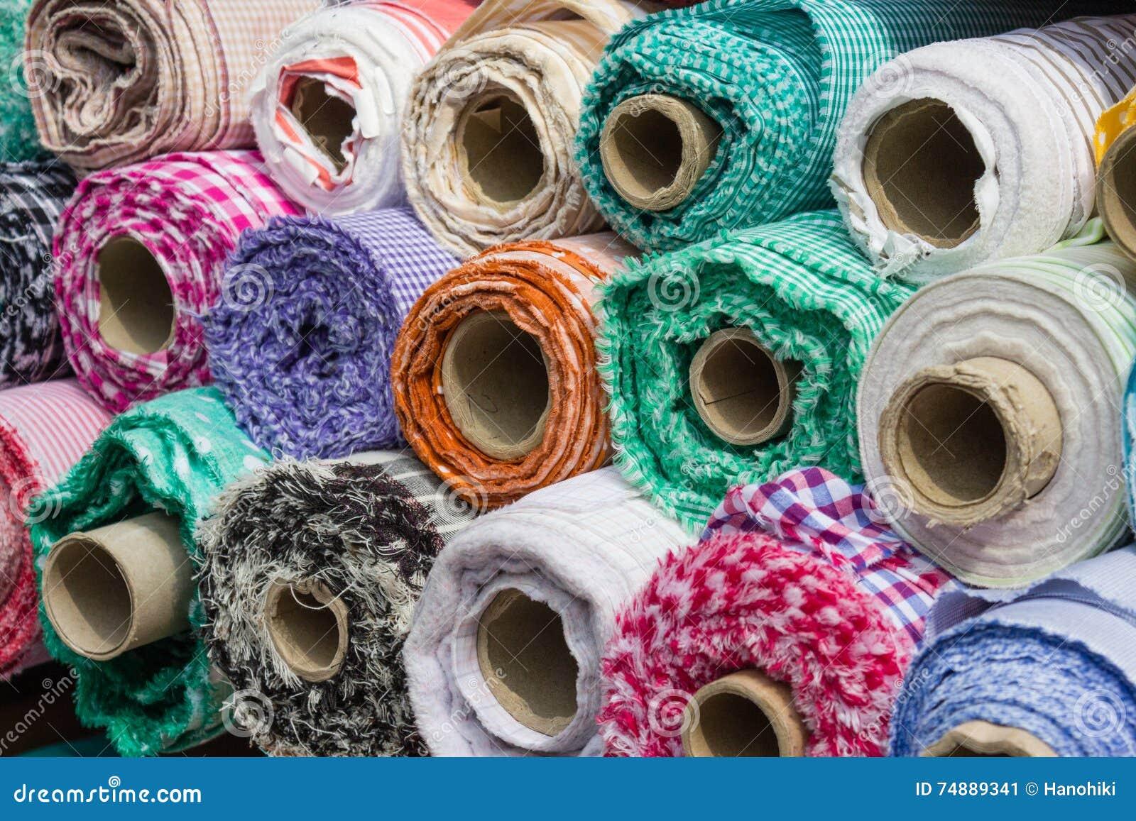 Рулоны ткани на стойле рынка, предпосылке текстильной промышленности