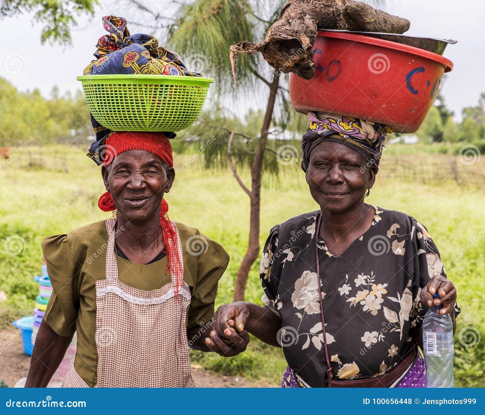 Рыбацкий поселок 2017 SEPT. 7, Lake Victoria, графство Kisumu, Кения, Африка Африканские женщины с полными ведрами сбалансировали