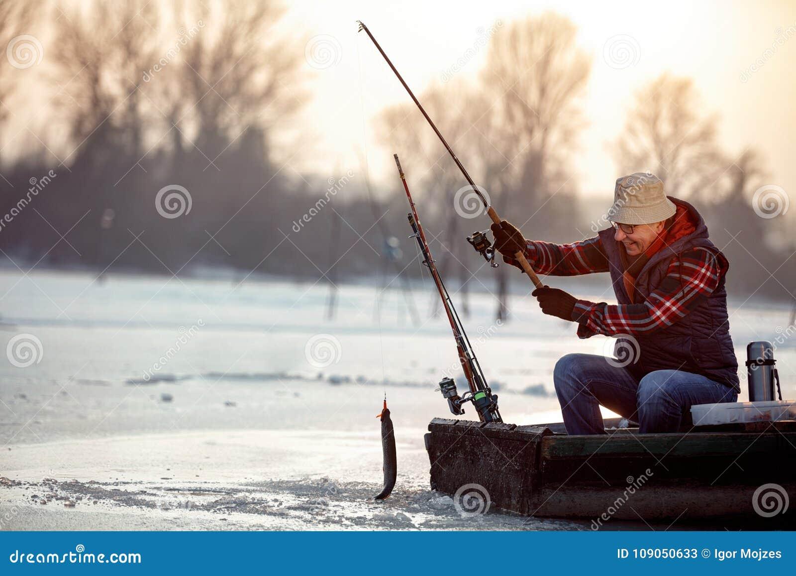 Рыбная ловля льда на рыбах задвижки рыболова замороженного озера усмехаясь