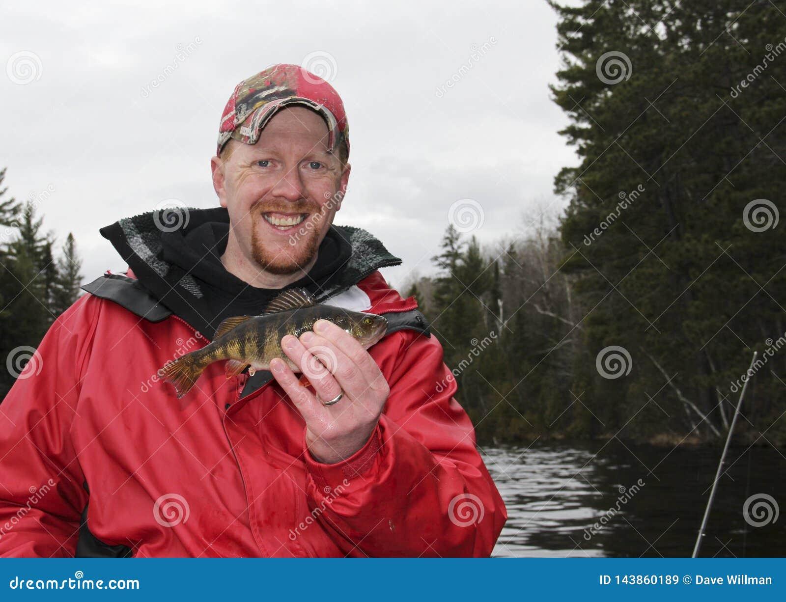 Рыболов в шлюпке держа окуня