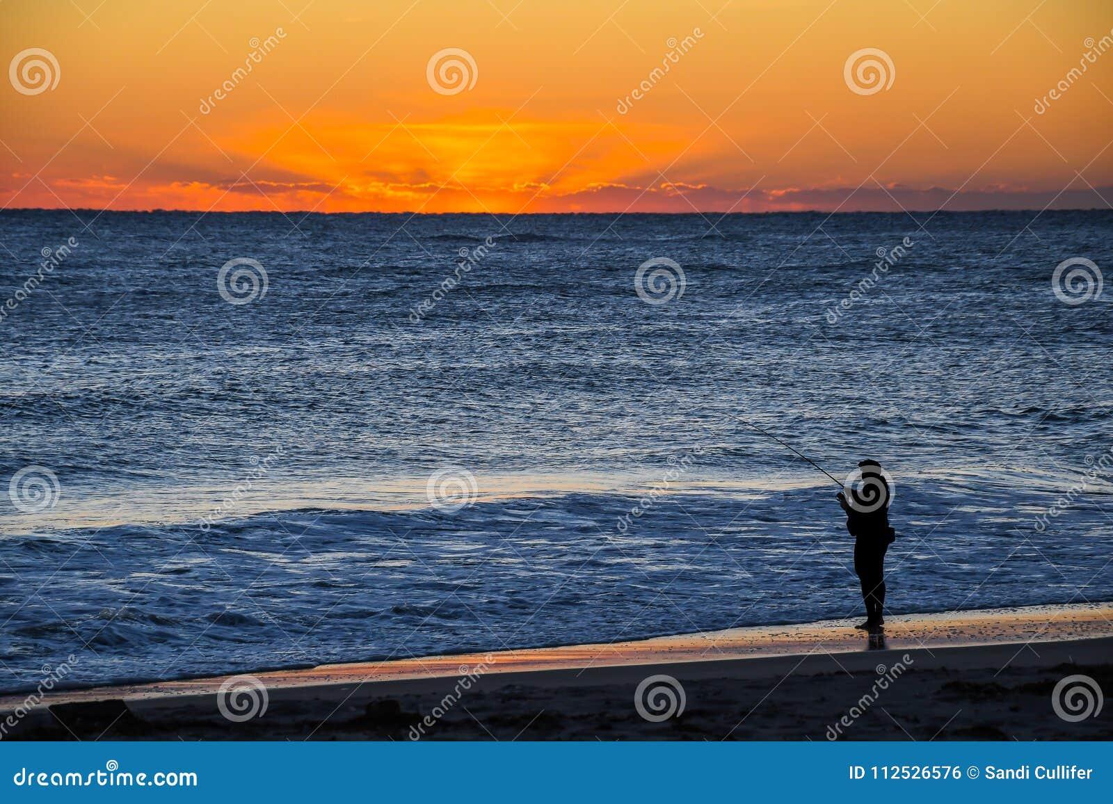 Рыболов прибоя наблюдая восход солнца