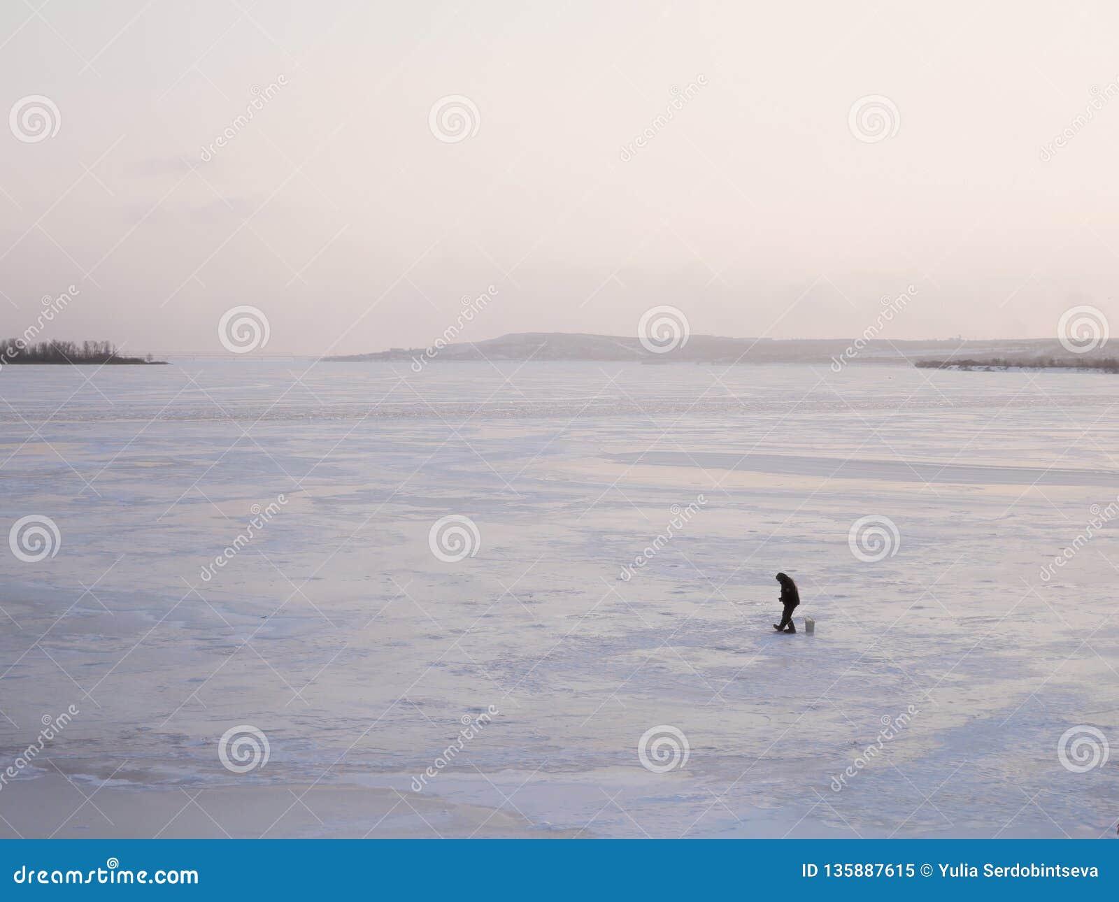 Рыболов сидит около отверстия льда на замороженном реке на заходе солнца