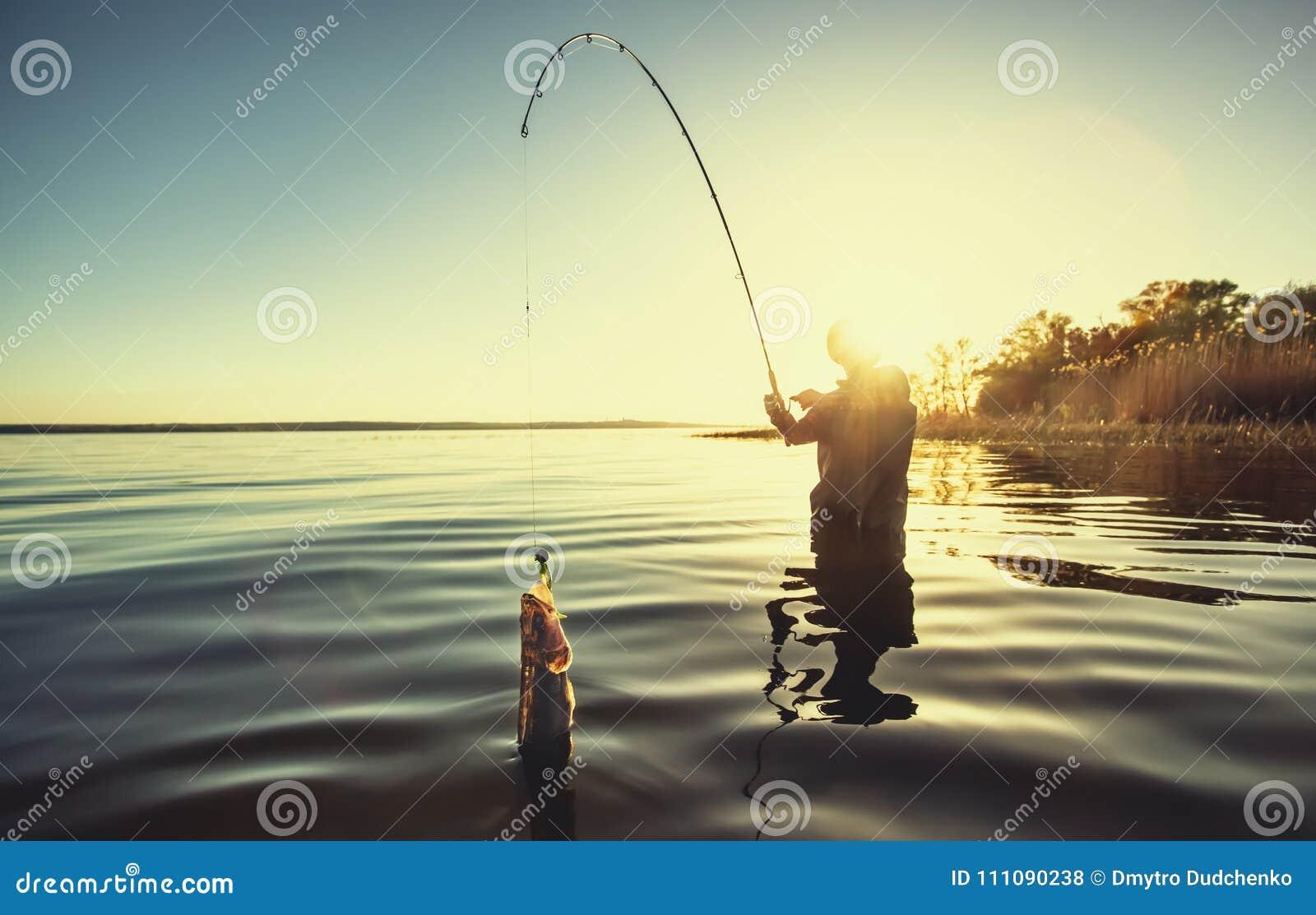 Рыболов с рыболовной удочкой в его руке и рыбе
