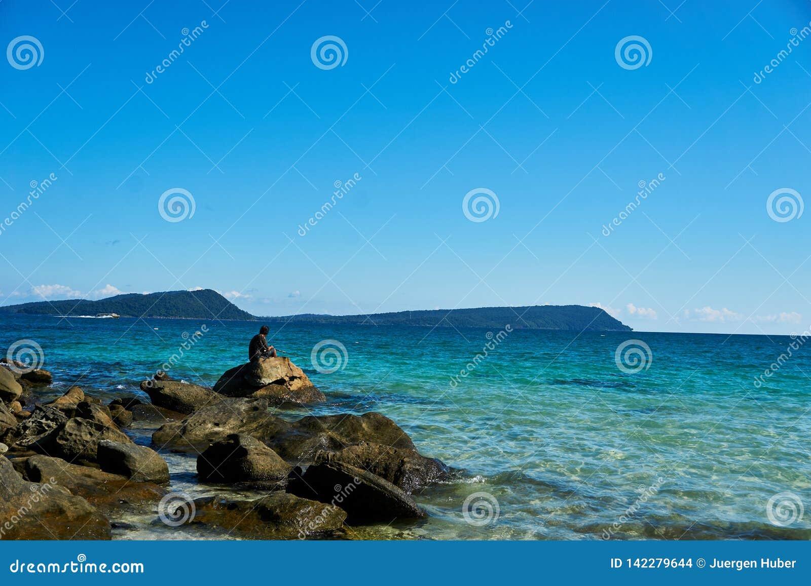 Рыболов удит на заливе Камбодже rong koh и сидит на камнях на пляже