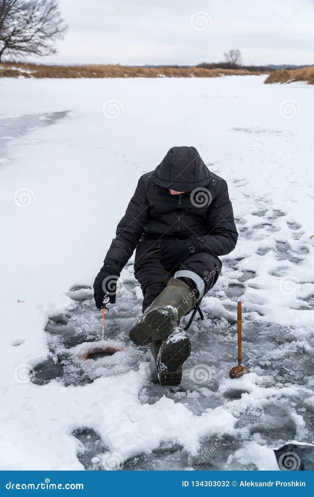 Рыболов улавливает рыбу на рыбной ловле зимы
