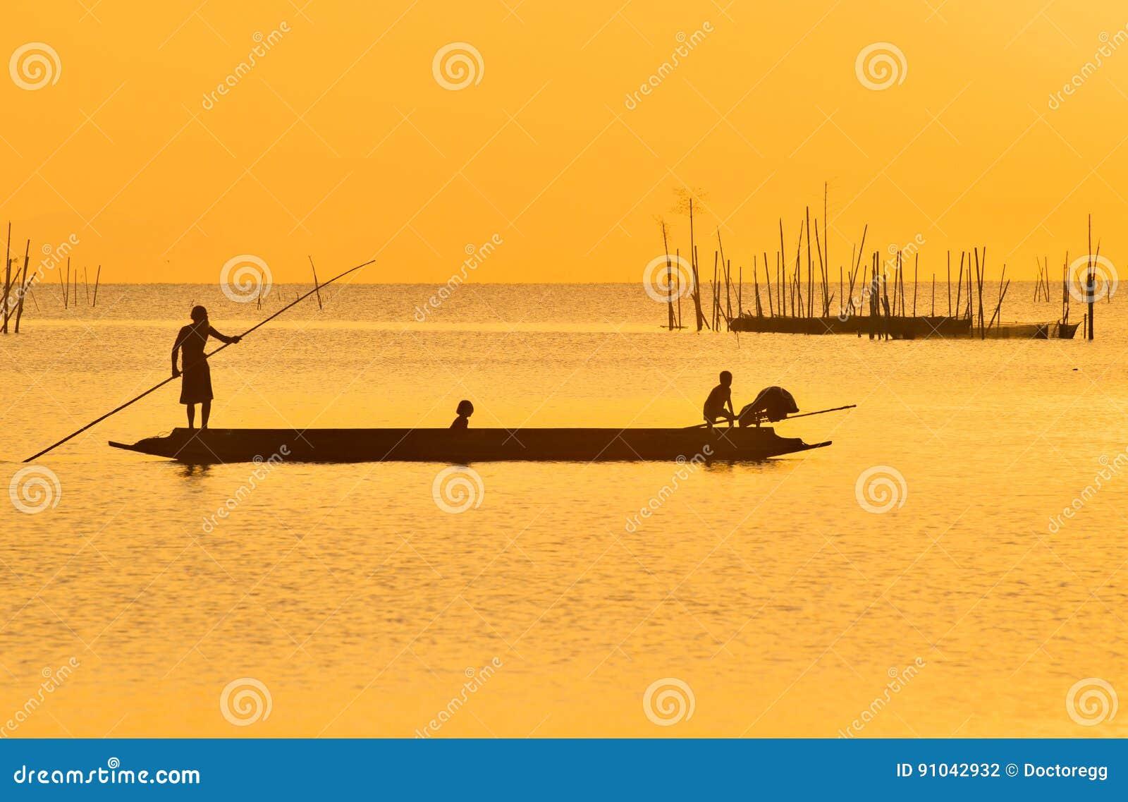 Рыболов бить его шлюпку после удить в заходе солнца на озере Songkhla, Songkhla, Souhtern Таиланда