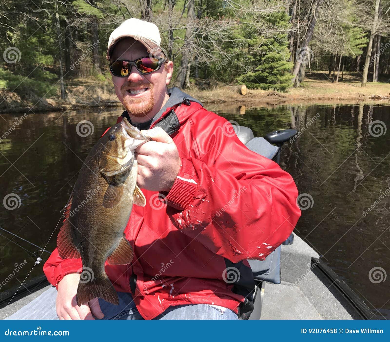 Рыболов держа баса Smallmouth