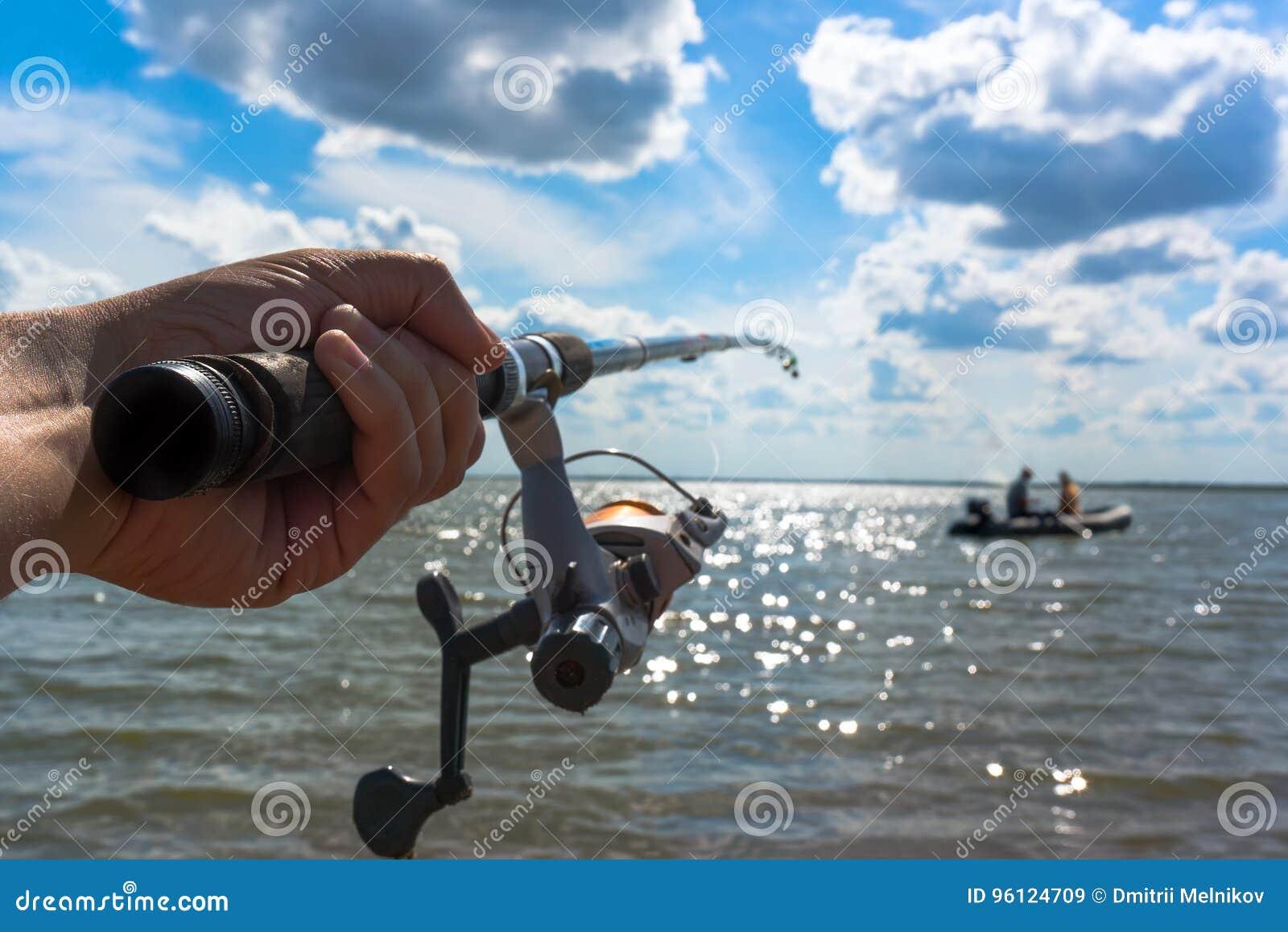 Рыболов рук держит закручивая штангу