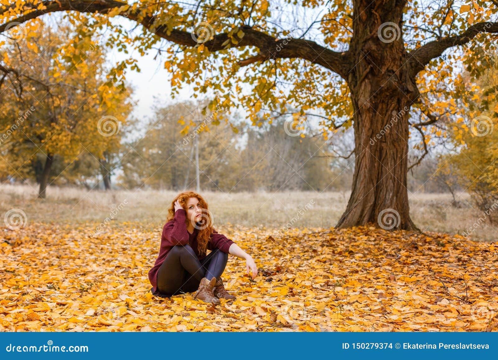 Рыжеволосая девушка в лесе осени сидя на желтых листьях