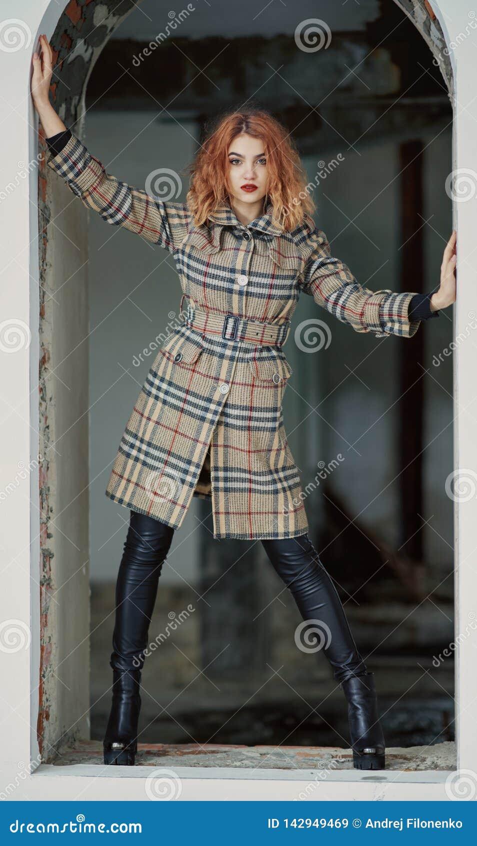 Рыжеволосая маленькая девочка в коротком checkered пальто и черных призонных брюках в высоких пятках представляет в получившемся