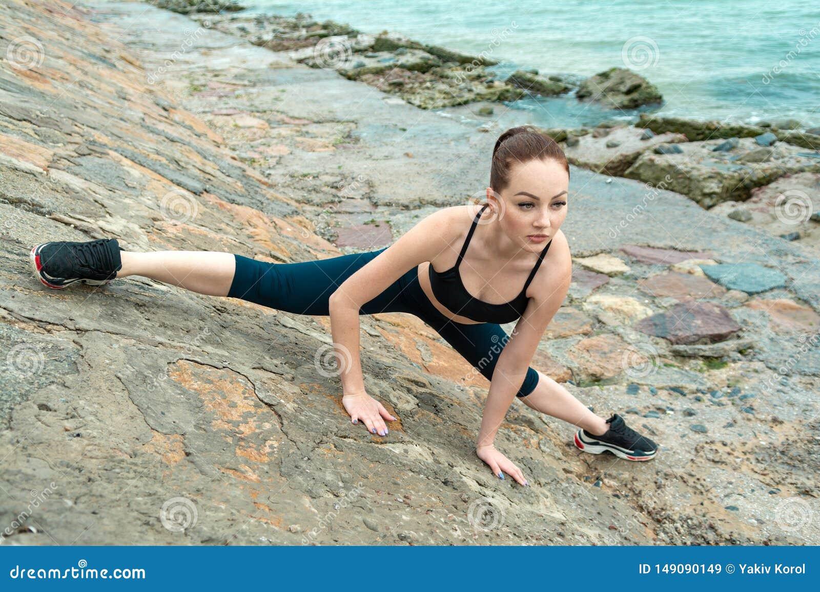 Рыжеволосая, молодая, атлетическая, красивая девушка принималась за гимнастику, бег на открытом воздухе Выполняет тренировки спор