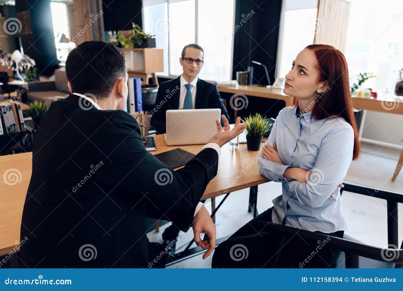 Рыжеволосая, неудовлетворенная женщина, при ее руки сжиманные совместно, слушает к человеку в костюме в офисе ` s юриста