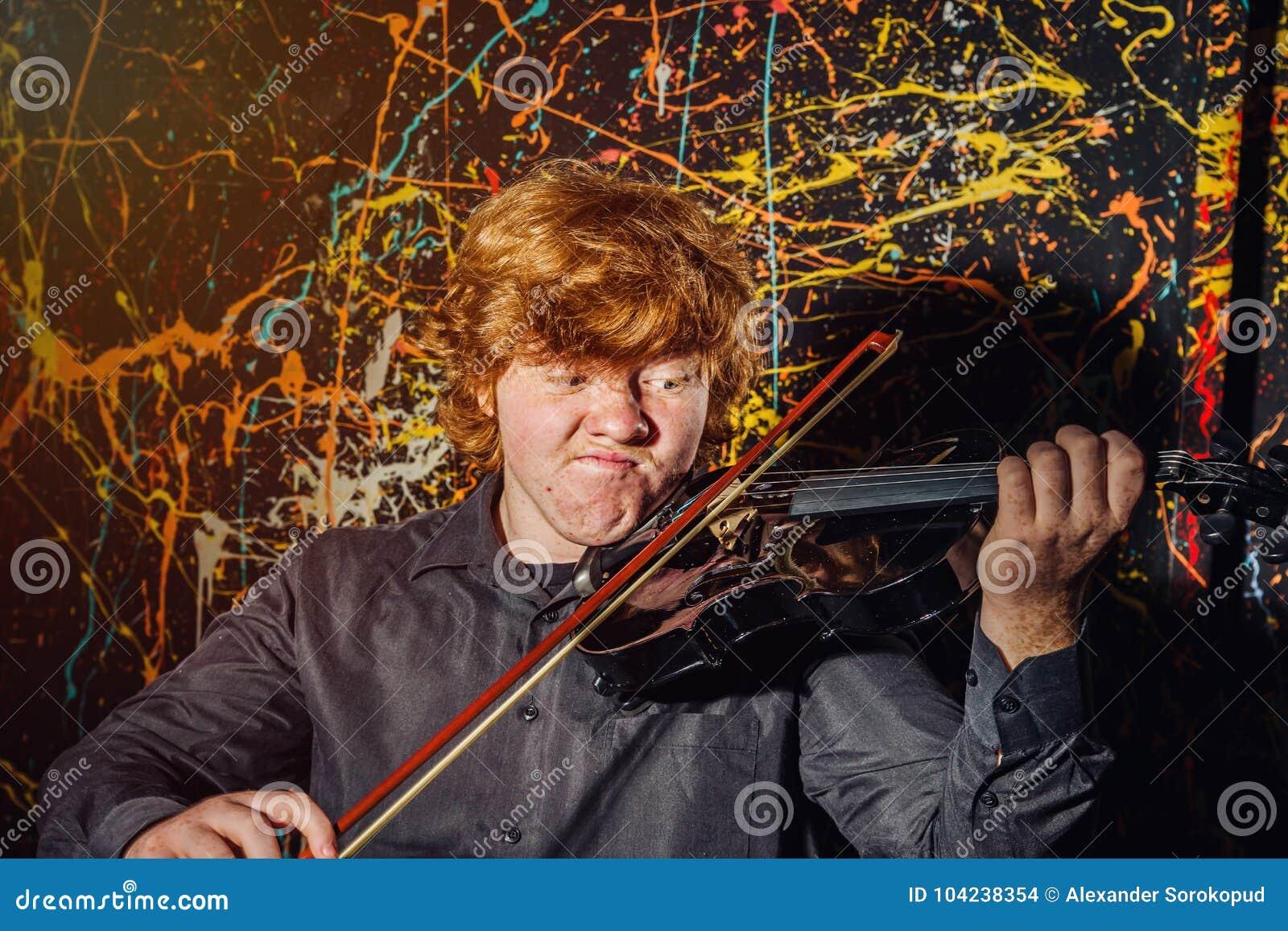 Рыжеволосый freckled мальчик играя скрипку с различными эмоциями o