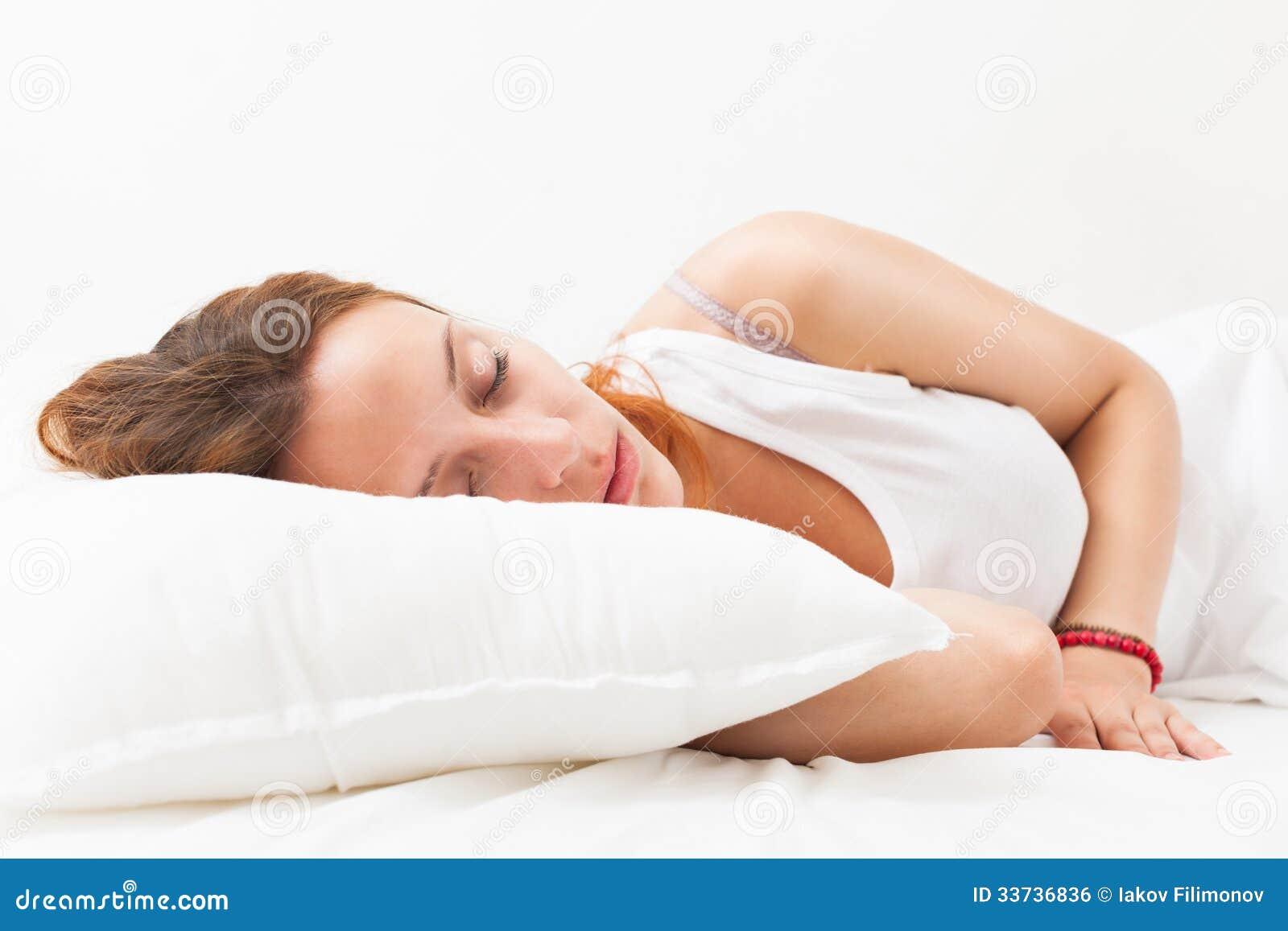 Рыжеволосая женщина спать на белой подушке в кровати дома
