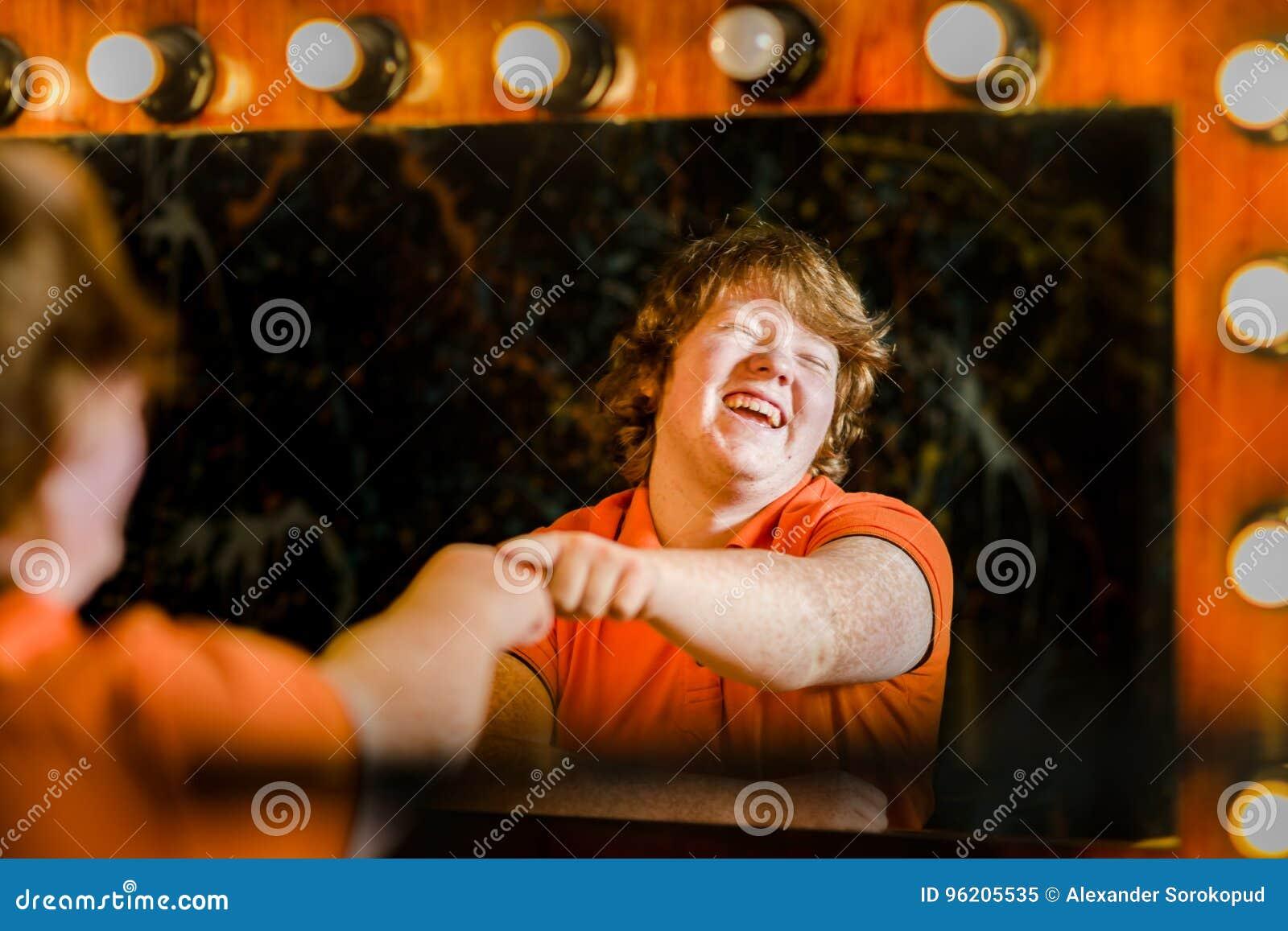 Рыжеволосый мальчик представляя перед зеркалом