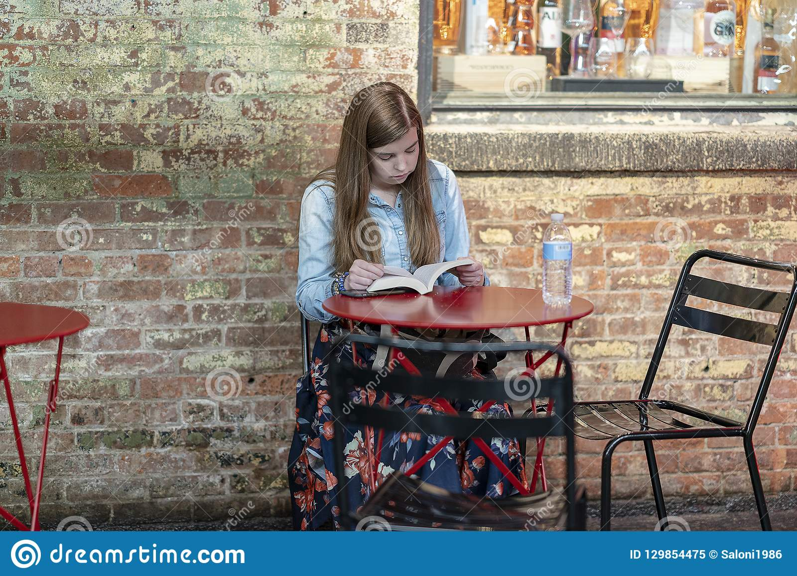 РЫНОК ЧЕЛСИ, НЬЮ-ЙОРК, США - 21-ое июля 2018: Книга чтения маленькой девочки в кафе